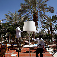 """Sudanese refugees perform maintenance in the Royal Beach Hotel on February 28 2011. The municipality hung 1,500 red flags around the city as a sign of warning and put up hundreds of banners reading: """"Protecting our home, the residents of Eilat are drawing the line on infiltration."""" Eilat Mayor Meir Yitzhak Halevi said that 10 percent of the city's population was currently made up of migrants and that the residents feel that the city has been conquered...Photo by Olivier Fitoussi."""