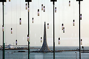 """The """"Beacon"""", a 60-meter contemporary interpretation of a lighthouse standing at the Red Sea entrance of the King Abdullah University of Science and Technology (KAUST) is seen framed by lighting fixtures hanging in the campus library September 21, 2009  in Thuwal, Saudi Arabia (about 80 kilometers north of Jeddah.) KAUST is an international, graduate-level research university dedicated to inspiring a new age of scientific achievement in the Kingdom that will also benefit the region and the world. Handout photo by Scott Nelson"""