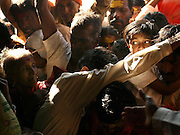 "A young girl's frightened eyes are visible amidst the crush of worshippers as her father tries to carry her into the Yellamma Temple in Saundatti, India, on the first day of the Yellamma Jatre (festival).  The Yellamma Jatre is an annual gathering of half a million Yellamma pilgrims who converge on the temple to worship the deity.  Amongst the rituals performed to appease Yellamma, young girls are dedicated as Devadasi or ""temple servants"".  These young girls are married to the deity and must spend their lives serving the deity which includes catering to the sexual needs of men in the community.  They may not marry a mortal and often end up working in brothels in India's urban centers. While the dedication ceremonies used to be performed in public at the Jatre and included parading the young girls naked through the crowds or covered in ""neem"" leaves, due to the Devadasi Prohibition Act, they are now performed in secret."
