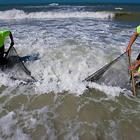 NAPLES, FL -- March 13, 2010 -- Jacqueline Haversat, 9, of Guilford, Connecticut, left, and Nate Hedrick, 5, of Summit, New Jersey, get help from counselor Gloria Rojas, left, and hotel naturalist, Randy Sarton, drag a net as they collect fish and crabs during the Nature's Wonders program at The Ritz-Carlton in Naples, Fla., on Saturday, March 13, 2010.  The three hour programs let kids experience a more involved, educational nature program while parents get free time to enjoy themselves sans kids.  (Chip Litherland for The Wall Street Journal)..KIDHOTEL