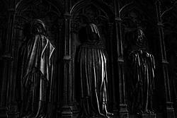 Three dark figures adorning the walls of Santa Eulalia Cathedral, Barcelona.