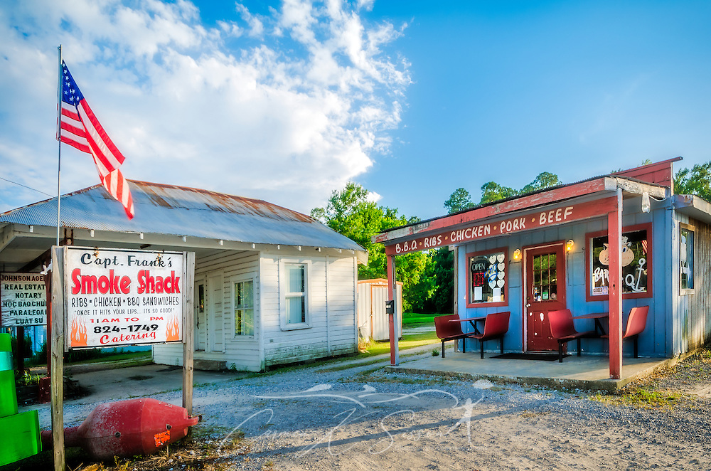 Capt. Frank's Smoke Shack is pictured beside Johnson Agency real estate office, Aug. 15, 2015, in Bayou La Batre, Alabama.(Photo by Carmen K. Sisson/Cloudybright)