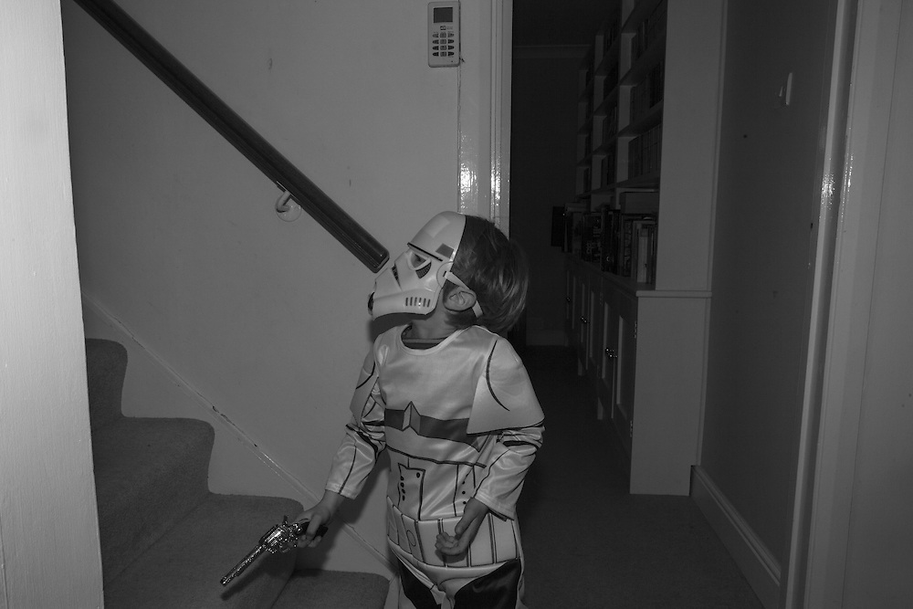 Ben wearing a Storm trooper outfit patrols the hallway armed with a toy gun during a playdate Thursday, April 2, 2015. Children and mothers inhabit a strange place that until a few years ago I didn't know existed. Even as I child I was oblivious to it. Now my days are spent with costumed Storm Troopers patrolling my hallways. My evenings are filled with dinners and bath times and bedtime reading and tantrums and so much else.  This is my new normal, and taking pictures makes me stop and look. This project has let me see photographs where before I thought there were none. It has allowed me to see the universality of my life and how it is reflected in so many other lives. (Elizabeth Dalziel) #thesecretlifeofmothers #bringinguptheboys #dailylife