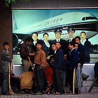 Porters waiting for the airport bus to arrive outside the city offices of a regional airline, with bamboo shoulder poles for carrying passenger baggage, another layer of service industry from the airline crew pictured in the advertising behind them...From China [sur]real © Mark Henley..