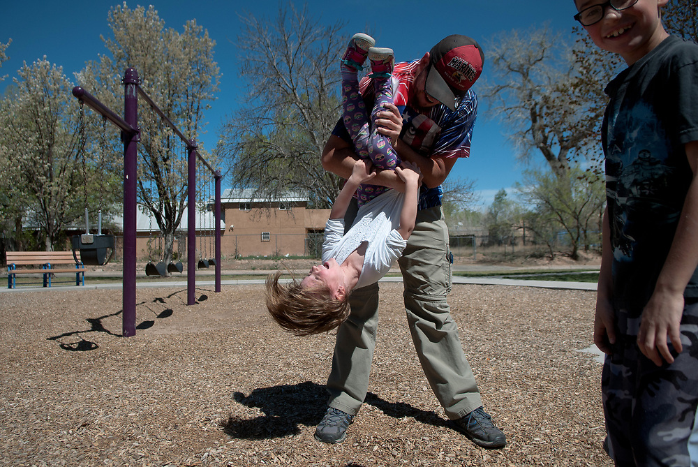 """mkb032417/metro/Marla Brose --  Joe Garcia holds his niece Riley Clark, 5, upside down while playing with his children, niece and nephew at Los Duranes Park in Albuquerque, N.M., Friday, March 24, 2017. Garcia spent several days with the children during this week's Spring Break. All the children go back to school Monday. """"I like doing fun things with my kids,"""" Garcia said. (Marla Brose/Albuquerque Journal)"""