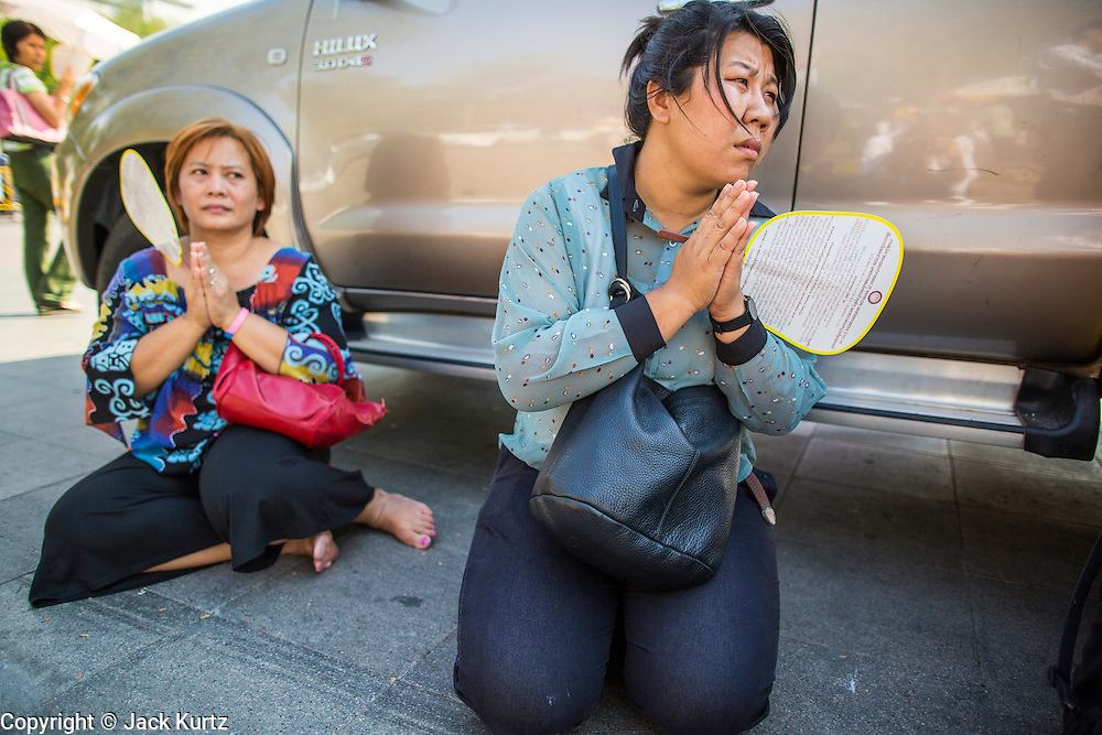 06 JANUARY 2013 - BANGKOK, THAILAND: Women pray in the shade of truck on a sidewalk in Bangkok during a ceremony for a piece of the Buddha's hair. The relic has been on display in Bangkok for about 10 years. There was a ceremony in Sanam Luang in Bangkok Sunday to honor the relic. People prayed for it and received blessings from Buddhist monks and Brahmin priests who presided over the service. The hair is being moved to Ayutthaya, where it will be displayed in a Buddhist temple. The piece of hair has been on loan to Thai Buddhists from a Buddhist temple in Sri Lanka.    PHOTO BY JACK KURTZ