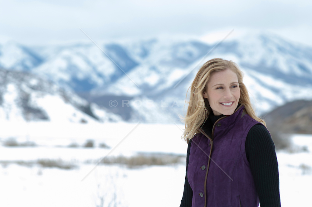 woman outdoors walking near snow covered mountains in Colorado