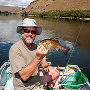 WA11813-00...WASHINGTON - Jim Johansen holds up a smallmouth bass ( Micropterus dolomieu) he caught in the Snake River near Lyons Ferry. (MR# J5)