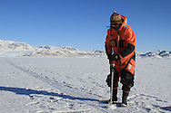 Ice physicist Sebastian Gerland (Norwegian Polar Institute)  augers fjord ice to collect data about the ice and its role in the carbon cycle; Kongsfjord, Svalbard, Norway.