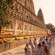 Buddhist pilgrims perform walking meditation around the Mahabodhi Temple, the site of the Buddha's enlightenment,  in Bodhgaya India.