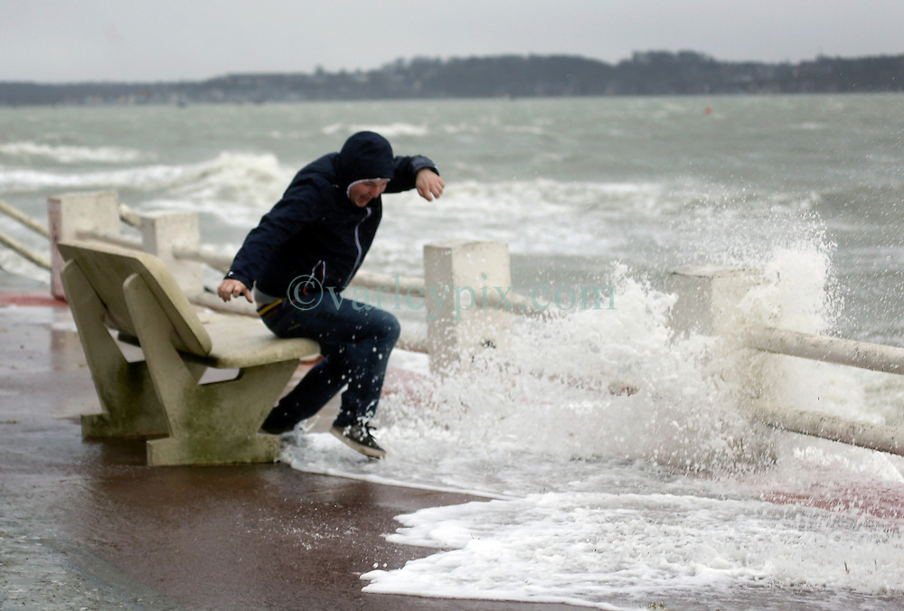 13 Jan 2017. Le Crotoy, Picardie, France.<br /> Gaetan Quenot jumps from a bench as the sea surges toward him as a fierce winter storm pushes the tide over the surge barrier on the Promenade Jules Noiret in the Bai Somme.<br /> Photo&copy;; Charlie Varley/varleypix.com