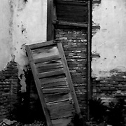 A door fallen from it hinges in an old room in Jerome, Arizona, shows the only exit is now bricked up.