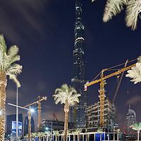 United Arab Emirates, Dubai, Construction cranes and palm trees loom above building sites and distant Burj Khalifa skyscraper at night