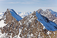 Longer days and warmer temperatures in spring begin to expose the seemingly endless ridgelines and craggy peaks of the snow covered Chugach Mountains in Chugach State Park near Anchorage in  Southcentral Alaska. Morning.