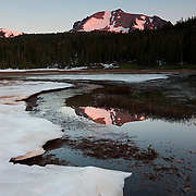 Lassen Peak, a 10,462 foot (3,189 meter) volcano in northern California, is reflected in the partially frozen Lake Helen. Lassen Peak is the southernmost volcano in the Cascade Range and last erupted from 1914-1917.