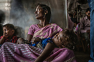 Mother cradles daughter on a commuter train in Chennai.  Despite a fairly extensive train system, Chennai's air pollution has been on the rise with the increase in the volume of cars.  Even though it is a coastal city, presumably with more vigorous breezes to clear the air, it temporarily passed Delhi in 2015 as the nation's most air polluted city.  Chennai, India.