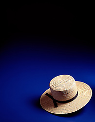 Amish mans straw hat on blue background with copy space.