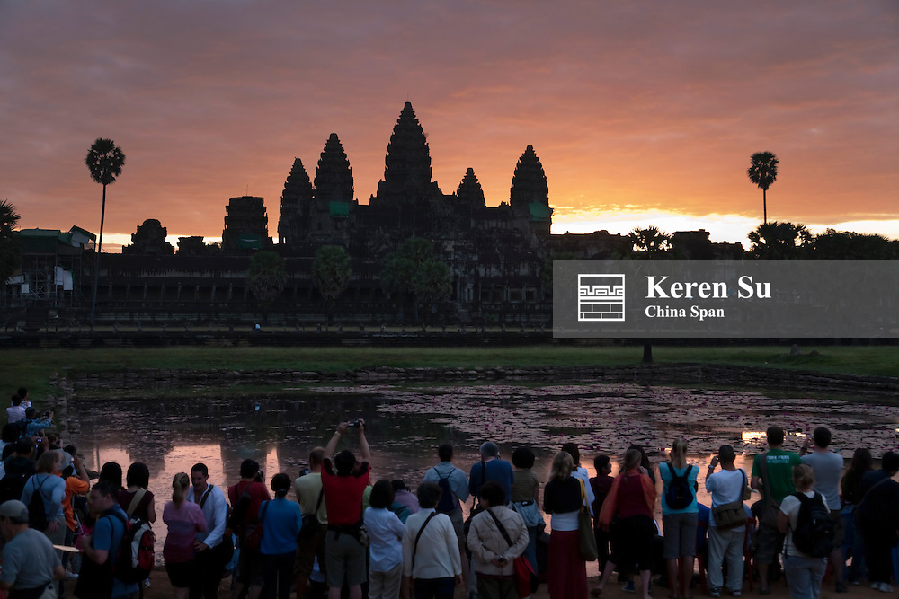 Tourists photographing the towers of Angkor Wat at sunrise, UNESCO World Heritage site.
