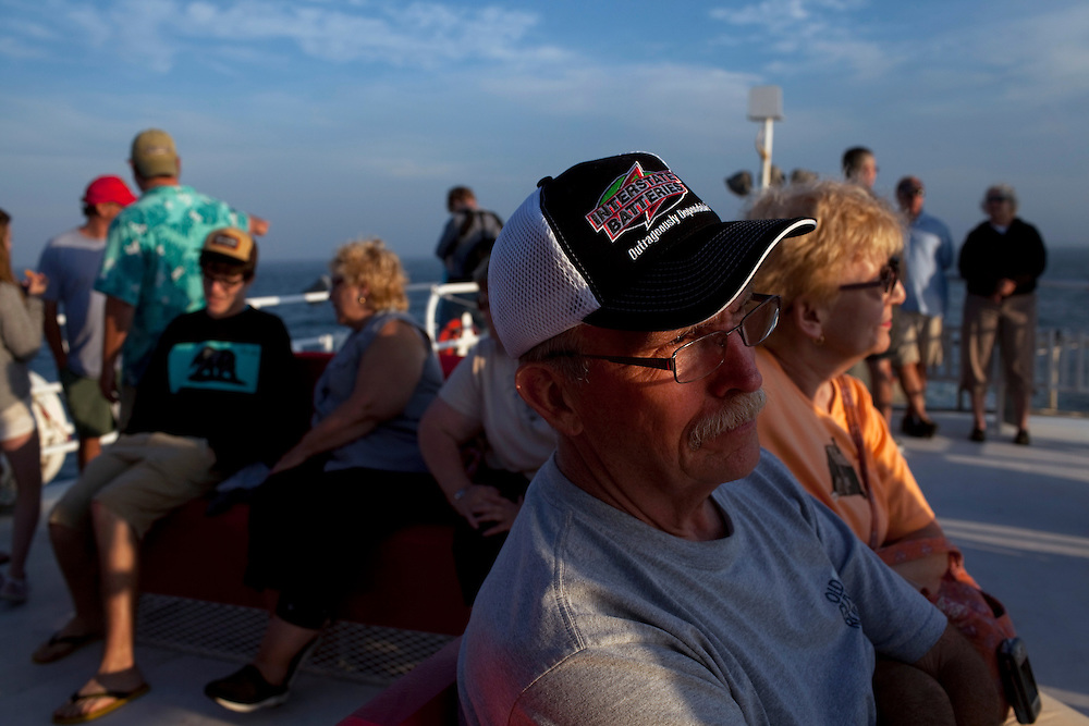 Long Beach Island, NJ - June 29, 2013 :  Lutheran church members Paul Anderson and Linda Bensen from Oak Lawn, IL, watch the sun set on the northern tip of Long Beach Island, NJ while sailing on the Miss Barnegat Light sunset cruise, on June 29, 2013. The Lutheran church group were on a mission trip to Long Beach Island to help with the post Superstorm Sandy clean up. People are returning to the beaches for the summer after recovery efforts post Superstorm Sandy.