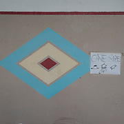 A diamond shaped painting on the wall, from the time when the building was used as a psychiatric clinic, at a now-closed refugee camp at the port of Lakki.<br /> <br /> The camp was opened by volunteers in the summer of 2015 and later that year UNHCR and MSF expanded it and provided additional tents, toilets and other facilities. The camp was closed soon after the opening of a 'Hotspot' (EU-run migrant's reception centres) camp in Lepida in February 2016.