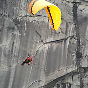 A man flies a motorized paraglider, or para motor past the Stawamus Chieftain and Shannon Falls.  Squamish BC, Canada.