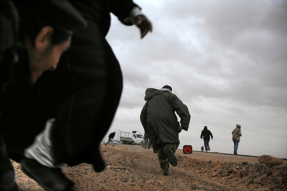 Rebel forces take heavy machine gun fire and artillery shelling during an air strike on Tuesday, March 8, 2011 on the road between Ras Lanuf and Bin Jiwad in Libya.  28 rebels were injured, and there were several casualties, the official number is currently unknown.