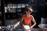 A woman works in the kitchen of a road side bus stop along the route from Bagan to Kawla in Mayanmar.