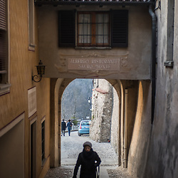 A woman walks through a narrow cobbled passage in Santa Maria Del Monte in Varese, Italy