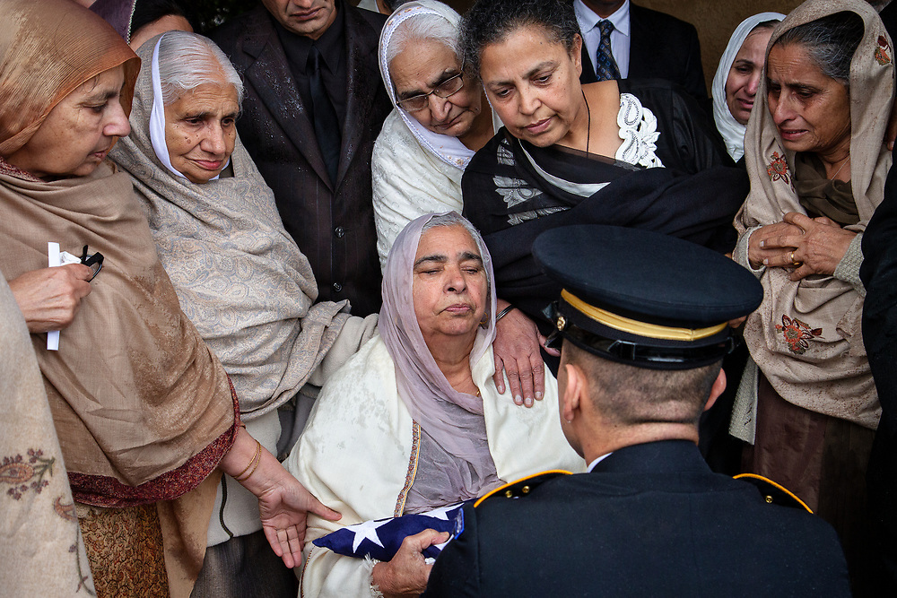 Lodi, California: A military honor guard presents Sukhwinder Kaur with the American flag that had draped the coffin of her son. Parminder Singh Shergill, who served in the US Army during the first Gulf War and suffered from post-traumatic stress disorder, was shot by police near his home on January 25, 2014. Officers claim he lunged at them with a knife; witnesses dispute the police account. Shergill was buried with military honors.