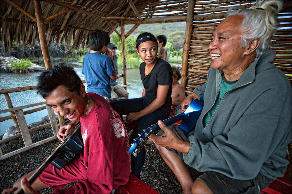"""Brother Nolan also referred to as """"Uncle No"""" plays with Kai Kahoaliki Fonseca during sunset kanikapila at the Ho'ea Initiative base camp located at the Keawanui Fishpond on Molokai."""