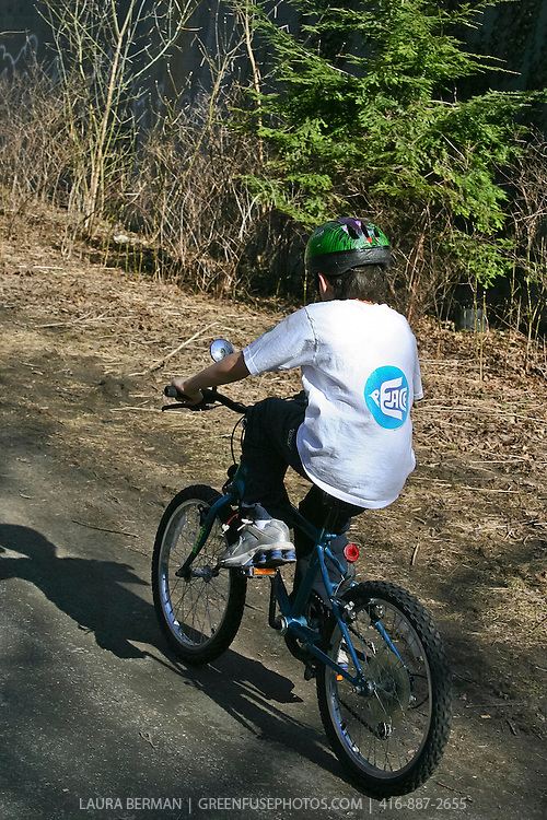 "A young bicycle rider with a ""Peace"" dove logo on his T shirt"