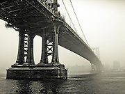 Manhattan Bridge pillars in the fog seen from the bank of the East River in DUMBO, Brooklyn, New York, 2008.