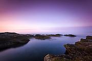 An early sunrise of pinks and purples from the rocky shoreline at Beavertail, Jamestown, Rhode Island.