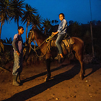 A young teenager sits on her brothers horse very easy in the morning before he heads out to gather up corn for the family in Pueblo Veracruz Oct 8, 2014. Central American Medical Outreach visit their family and two other families who all live nearby on occasion to make sure they are doing well.