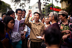 An elder Vietnamese woman gives a speech to a crowd near Hoan Kiem lake, Hanoi, Vietnam, Southeast Asia