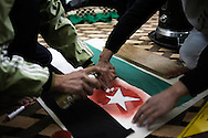 SYRIA - Al Qsair. In many houses, women and man of Al Qsair give their help for the revolution making scarves, hats and flags and writing banners for demonstration, with the colors of the old Syrian flag (the flag of the revolution) black, green and white with three red stars in the middle, on January 25,  2012. Al Qsair is a small town of 40000 inhabitants, located 25Km south-west of Homs. The town is besieged since the beginning of November and so far it counts 65 dead. ALESSIO ROMENZI