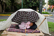 27 JULY 2003 - MEXICO CITY, MEX: A homeless girl sleeps in a shelter made from an umbrella and plastic sheeting in Mexico City, Mexico. PHOTO BY JACK KURTZ