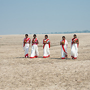 Hundu women arrive to perform religious rituals on the bank of river Ganga, held sacred by followers of Hinduism. Millions of Hindus bathe in the river daily if living close, or annually at special holy places (tirthas). Many cast the ashes of their dead into its waters, and cremation temples are found along its banks in many (pilgrimage) places.