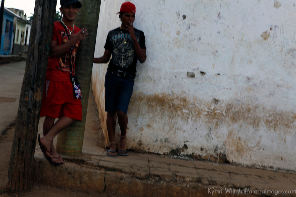 Central America, Cuba, Remedios. Teenage boys sneak a smoke on the street corner in Remedios. Note: Unsharp image.