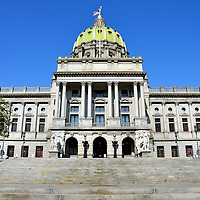 Pennsylvania State Capitol Building in Harrisburg, Pennsylvania<br /> The fifth and current Pennsylvania State Capitol in Harrisburg has been a masterpiece since it was completed in 1906. At the base of the granite portico are large bronze doors with historic state scenes. Embracing the edges are two beautiful sculptures in Italian marble. The lime green, terra cotta tile dome with 48 portholes resembles St. Peter&rsquo;s Basilica. On top is a gilded statue of a woman standing on an orb and holding a staff. She symbolizes justice and her name is Commonwealth. Pennsylvania became the 2nd state on December 12, 1787.