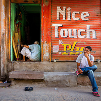 "The young boy in India sits in front of the shutter of a storefront that is painted with the words ""nice touch""."