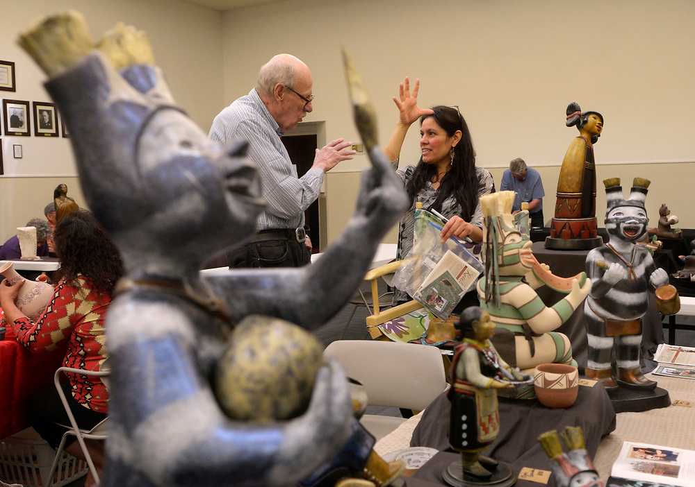 """gbs031917a/ASEC -- Hugh Witemeyer of Albuquerque, left, talks with artist Kathleen Wall of Jemez Pueblo at the Jemez Pueblo Artisan Fair at Congregation Albert on Sunday, March 19, 2017. Wall works in bronze and pottery. The bronze piece in the foreground is """"Koshare Stars.""""  This was Congregation Albert Bortherhood's 2nd Annual Jemez Pueblo Artisan Fair in conduction with the Jemez Arts and Crafts Association."""