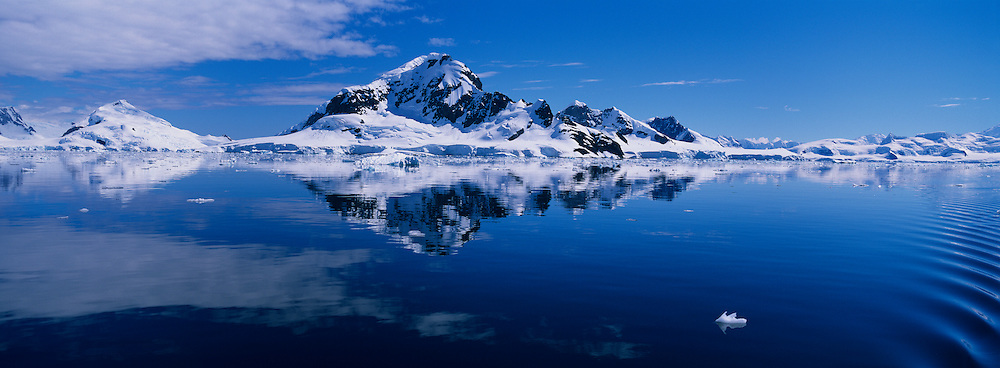 Antarctica, Paradise Bay, Glacier-covered peaks on Bryde Island reflected in still waters along Antarctica Peninsula