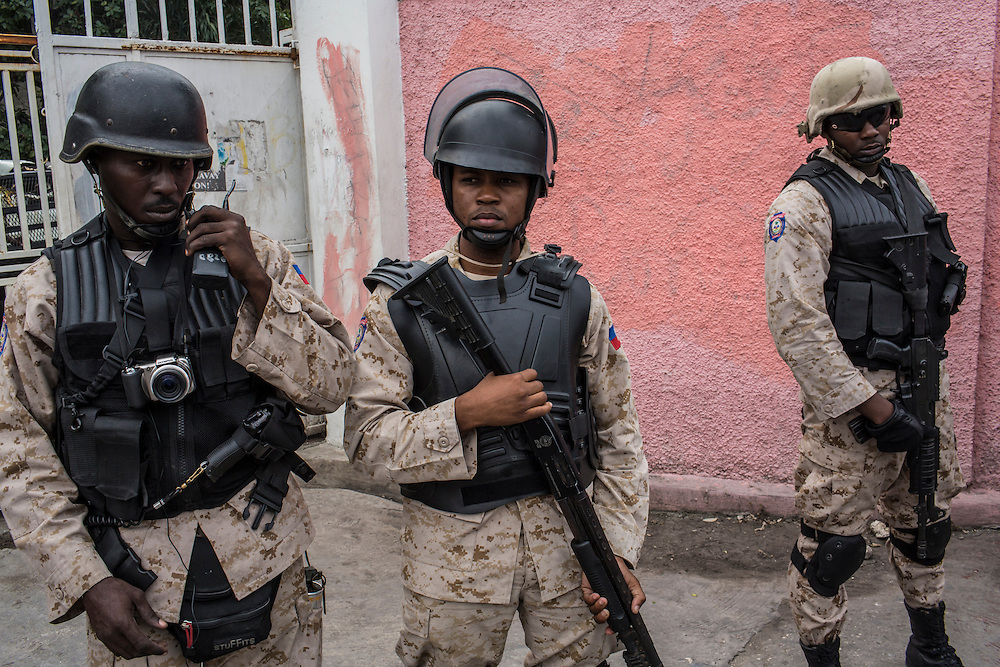 Police guard the Justice Ministry during an anti-government protest on Tuesday, December 16, 2014 in Port-au-Prince, Haiti. President Michel Martelly was elected in 2010 with great hope for reforms, but in the wake of slow recovery and parliamentary elections that are three years overdue, his popularity has suffered tremendously, forcing Prime Minister Laurent Lamothe to resign.