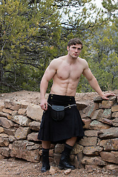 shirtless muscular man in a kilt outdoors by a stone wall