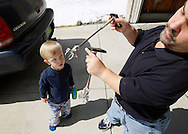 Chris Kotzian (R) shows the extensions he uses on his car's gas pedal and brake as his son Adam, 6 watches at their home in Thornton, Colorado March 25, 2010.  Chris and Adam are both achondroplasia dwarfs. Chris is active in the Little People of America, the only dwarfism support organization that includes all 200+ forms of dwarfism.  REUTERS/Rick Wilking (UNITED STATES)