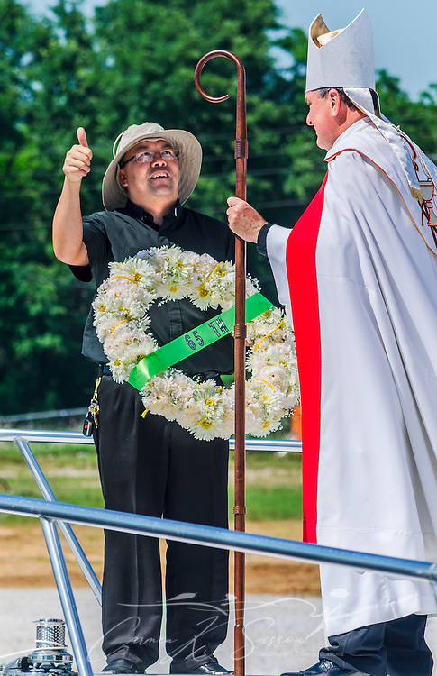 The Rev. Bieu Nguyen, pastor of St. Margaret's Catholic Church, holds a ceremonial wreath as he talks with Catholic Archbishop Thomas J. Rodi during the 65th annual Blessing of the Fleet in Bayou La Batre, Alabama, May 4, 2014. The first fleet blessing was held by St. Margaret's Catholic Church in 1949, carrying on a long European tradition of asking God's favor for a bountiful seafood harvest and protection from the perils of the sea. The highlight of the event is a blessing of the boats by the local Catholic archbishop and the tossing of a ceremonial wreath in memory of those who have lost their lives at sea. The event also includes a land parade and a parade of decorated boats that slowly cruise through the bayou. (Photo by Carmen K. Sisson/Cloudybright)