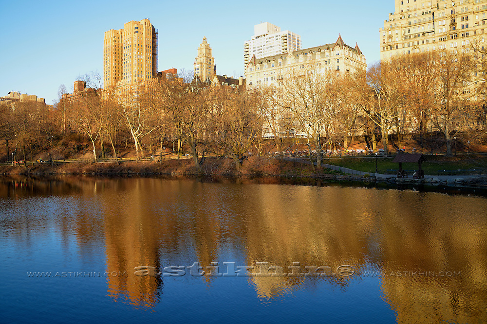 Reflection of The Dakota Apartments and Majestic Apartments on water in Central Park New York City.