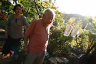 Tsutomu Yamaguchi (foreground, with daughter in background) in his garden, talking of the days when he lived through two atomic bombings. Photographed on Wednesday May 25th 2005. Yamaguchi was in Hiroshima on the day of the first atomic bombing, 6th Aug. 1945, and also in Nagasaki three days later on the day of the second atomic bombing of Japan by US Military.