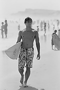 Surfer carrying his surfboard walking on a beach in Montauk, NY